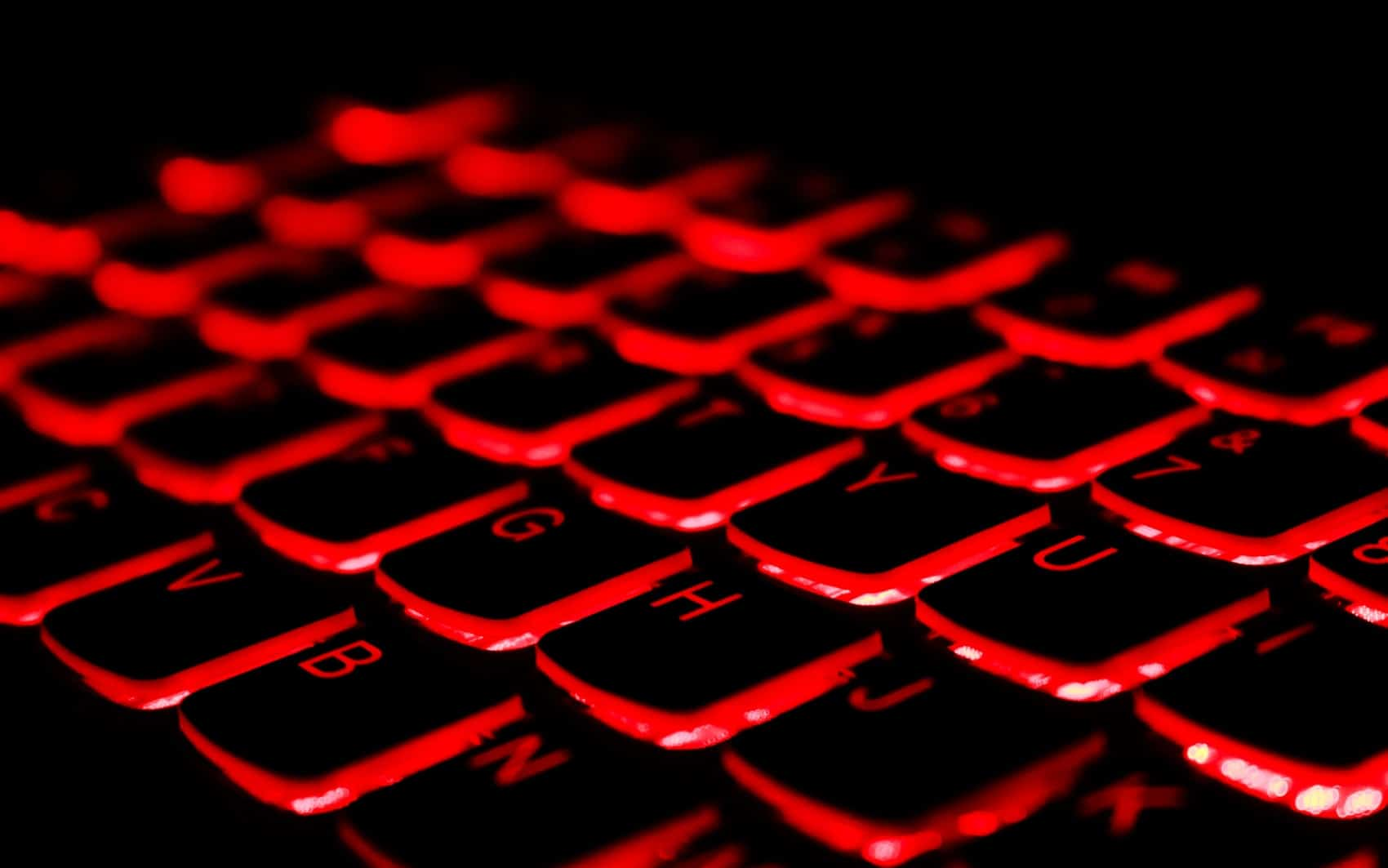 Computer keyboard in the dark, glowing red